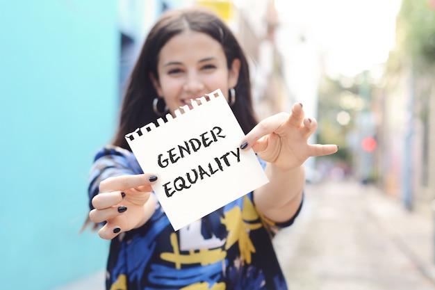 Mulher que mostra um bloco de notas com a igualdade de gênero do texto. Foto Premium