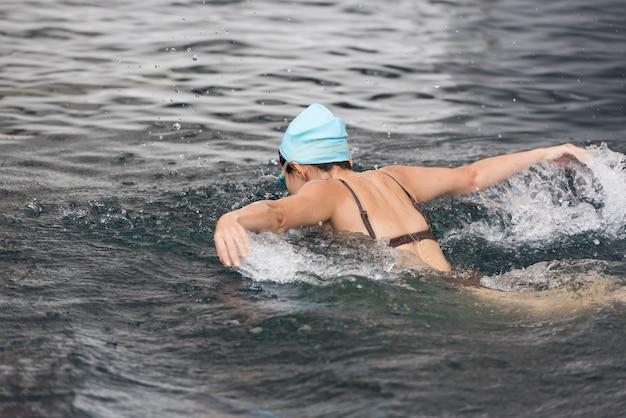 Mulher que nada o curso de borboleta em uma piscina. Foto Premium