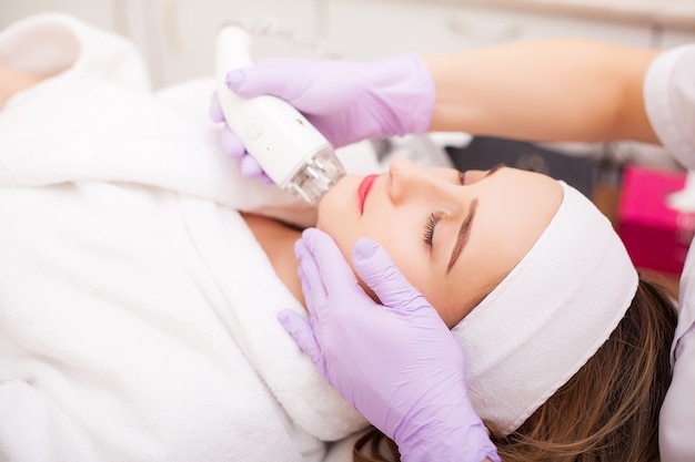 Mulher que obtém a massagem do hardware do lpg na clínica da beleza. esteticista profissional trabalhando Foto Premium