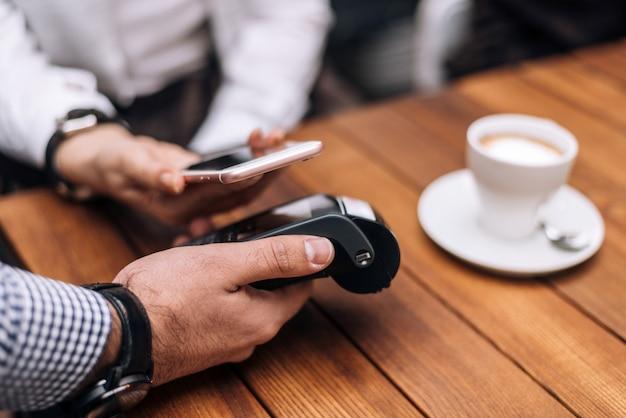 Mulher que paga pelo café pelo telefone móvel no restaurante. Foto Premium