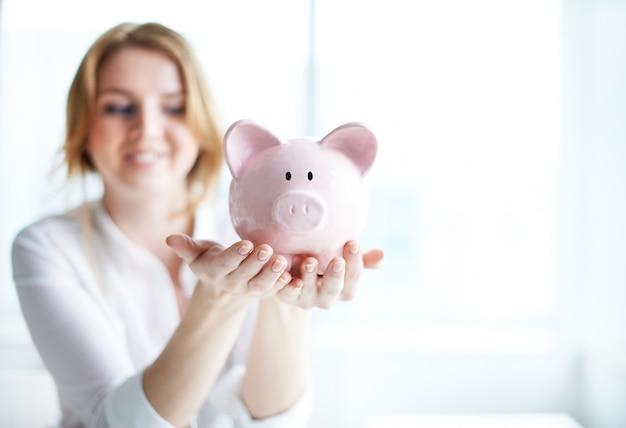 Mulher que prende um banco piggy Foto gratuita