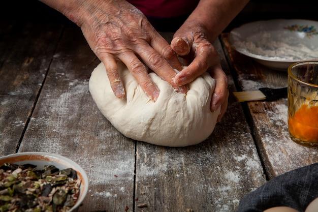 Mulher que prepara a massa em close-up de madeira mesa. Foto gratuita