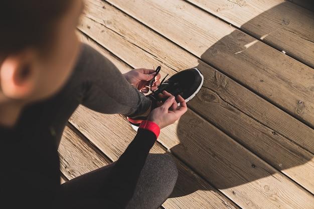 Mulher que prepara seus tênis antes de começar a correr Foto gratuita