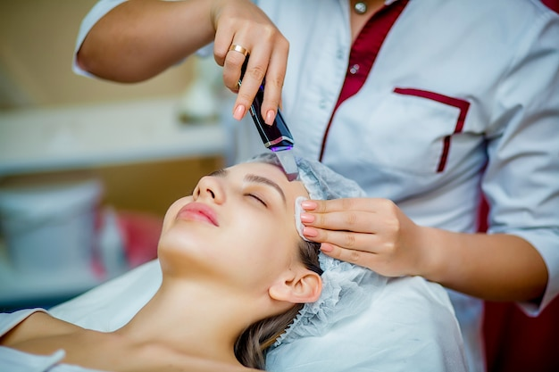 Mulher que recebe a esfoliação facial ultra-sônica no salão da cosmetologia. Foto Premium