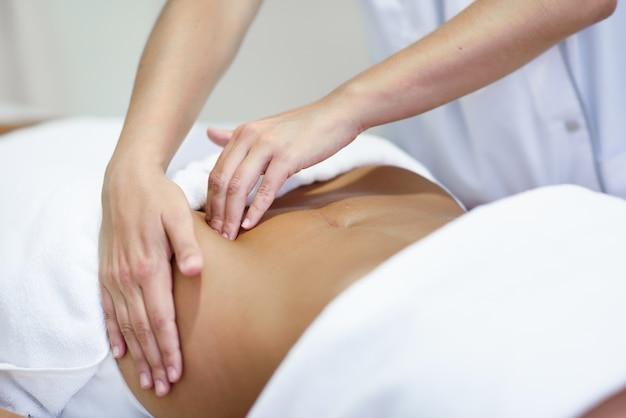 Mulher que recebe uma massagem do ventre no salão de spa Foto gratuita