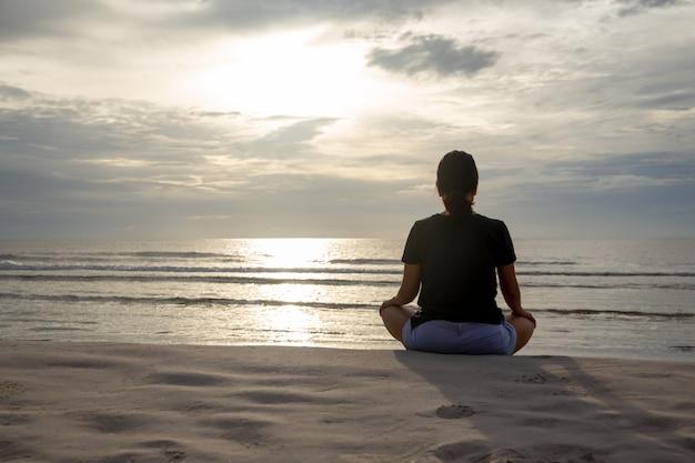 Mulher que senta-se na pose da meditação na praia na manhã Foto Premium