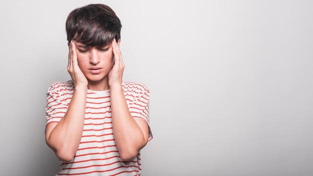 Mulher que sofre de dor de cabeça isolado fundo branco Foto gratuita