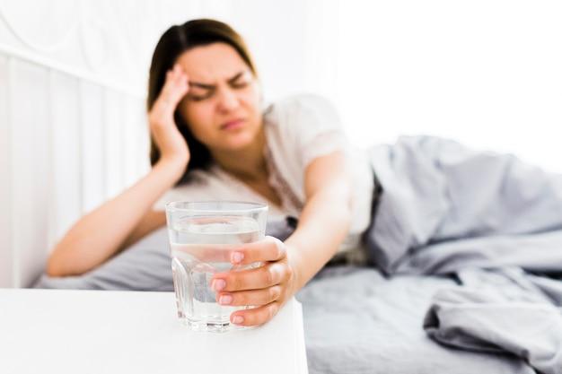 Mulher que sofre de dor de cabeça tomando um copo de água Foto gratuita