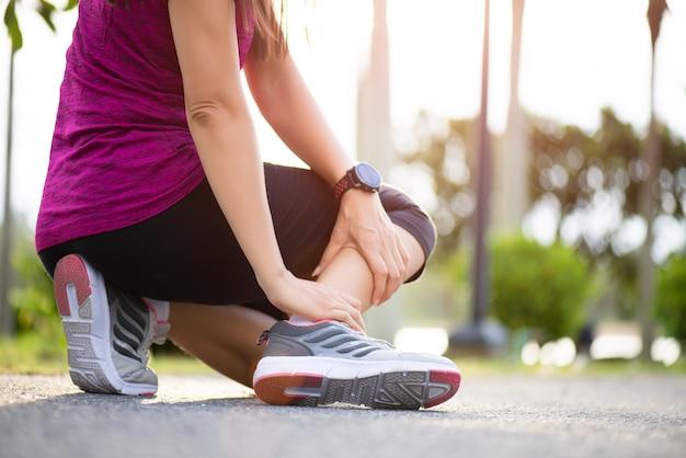 Mulher que sofre de uma lesão no tornozelo durante o exercício e correndo Foto Premium