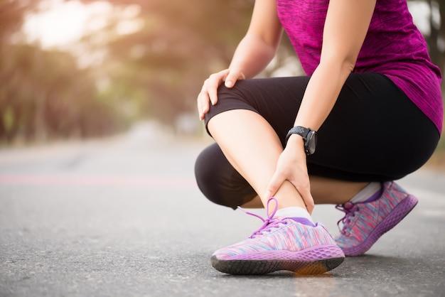 Mulher que sofre de uma lesão no tornozelo durante o exercício Foto Premium