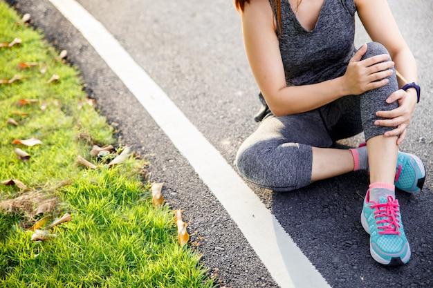 Mulher que sofre de uma perna dolorosa enquanto corre no parque. Foto Premium