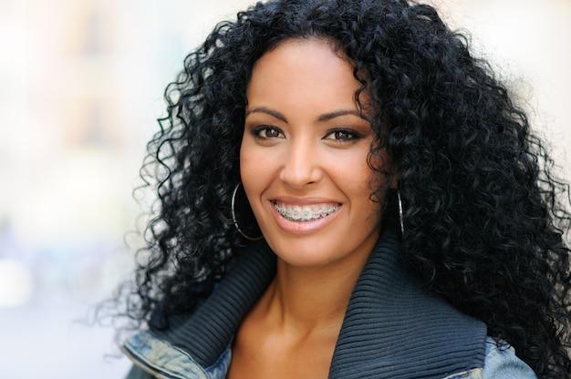 Mulher que sorri com aparelhos nos dentes Foto gratuita