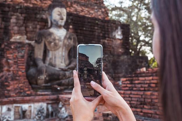 Mulher que tira uma foto com o telefone em pé a imagem de buda de wat mahathat no parque nacional de sukhothai na tailândia. Foto Premium