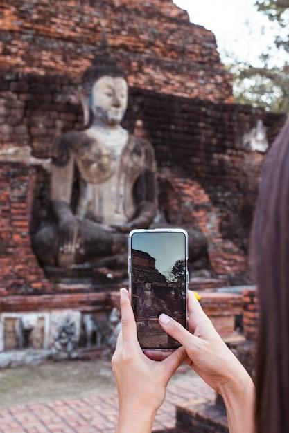 Mulher que tira uma foto vertical com o telefone de tela em pé buddha em wat mahathat no parque nacional de sukhothai. Foto Premium
