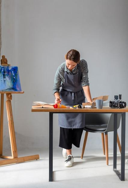 Mulher que trabalha em estúdio com pintura Foto gratuita