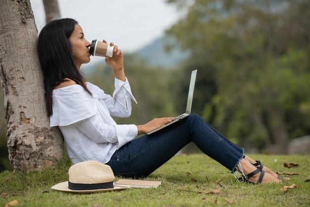 Mulher que trabalha em um laptop na natureza Foto gratuita