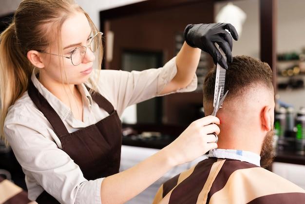 Mulher que trabalha na barbearia Foto gratuita