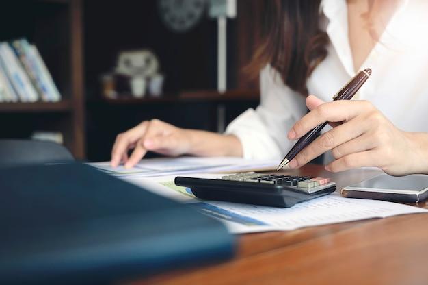 Mulher que usa a calculadora na mesa de escritório. Foto Premium
