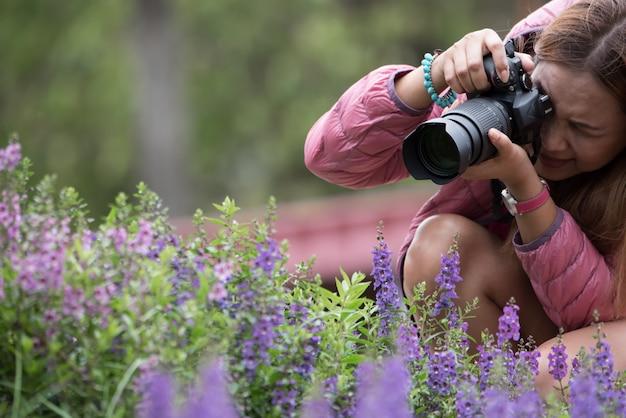 Mulher que usa a câmera de dslr que toma a flor no parque. Foto Premium