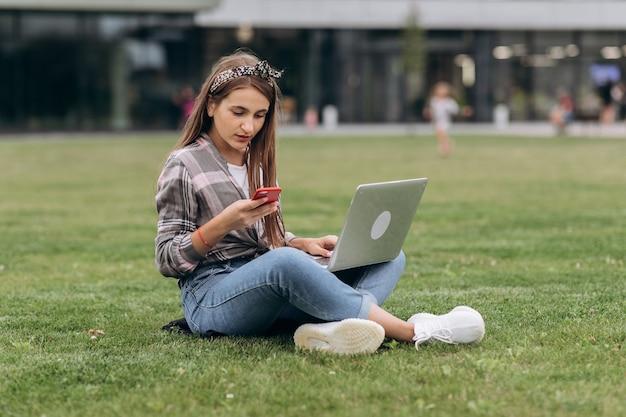 Mulher que usa o computador em gramas verdes no parque. trabalho freelance ao ar livre ou conceito de relaxamento Foto Premium