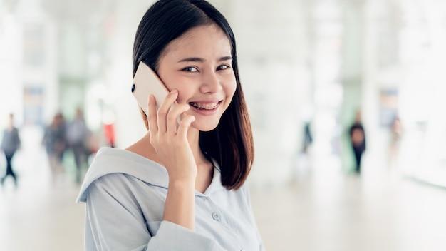 Mulher que usa o smartphone em áreas públicas da escadaria, durante o tempo de lazer. o conceito de usar o telefone é essencial na vida cotidiana. Foto Premium