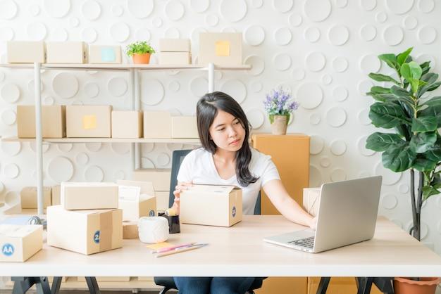 Mulher que verifica a ordem de compra no laptop Foto Premium