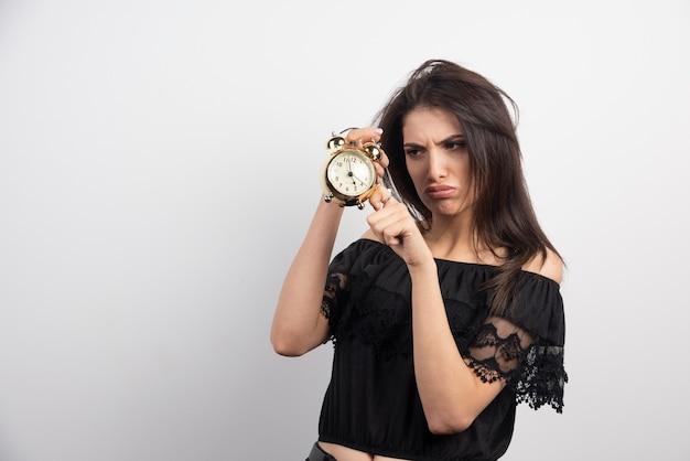 Mulher rabugenta segurando o relógio Foto gratuita