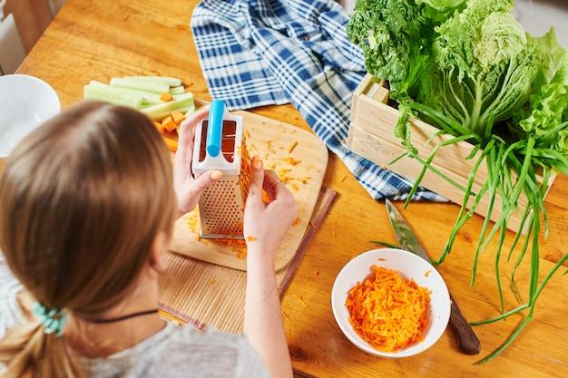 Mulher rala as cenouras em uma placa de madeira Foto Premium