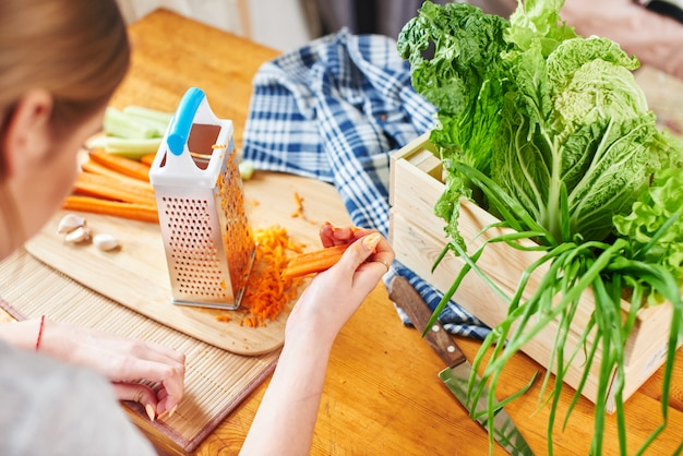 Mulher rala as cenouras na cozinha Foto Premium