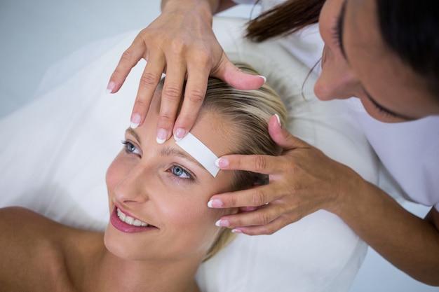 Mulher recebendo as sobrancelhas em forma Foto gratuita