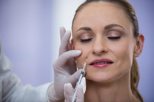Mulher recebendo injeção de botox Foto gratuita