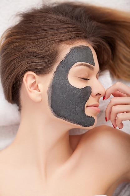 Mulher recebendo máscara facial no salão de beleza Foto Premium