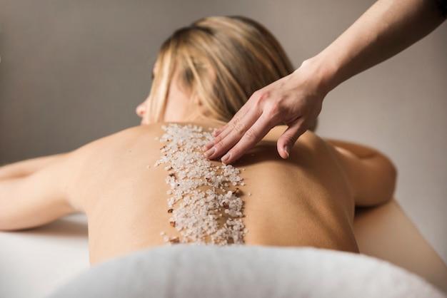 Mulher recebendo massagem com sal do mar no spa Foto gratuita