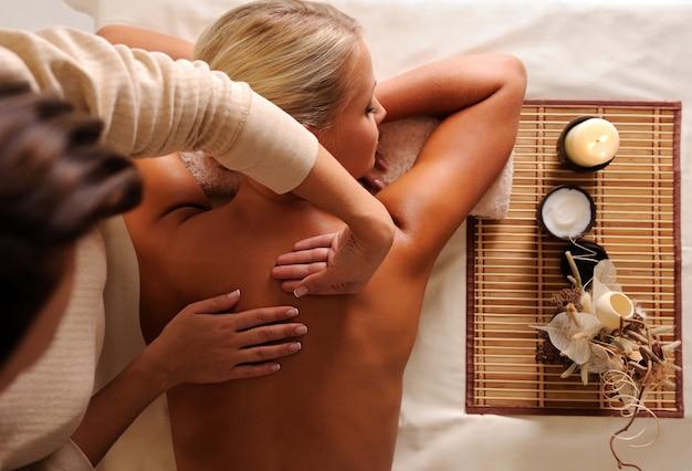 Mulher recebendo massagem relaxante em vista de alto ângulo do salão de beleza Foto gratuita
