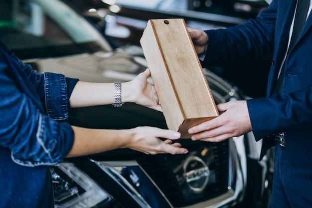 Mulher recebendo parcela de madeira em uma sala de exposições de carros Foto gratuita