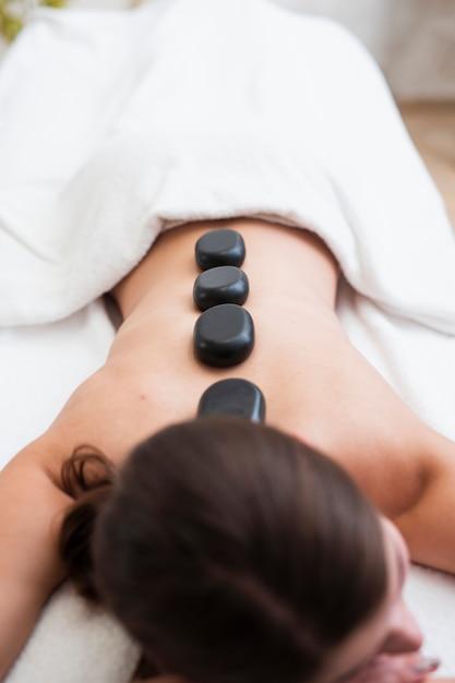 Mulher recebendo pedras aquecidas nas costas no spa Foto gratuita