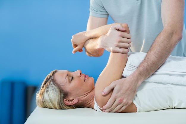 Mulher recebendo terapia do ombro do fisioterapeuta Foto Premium