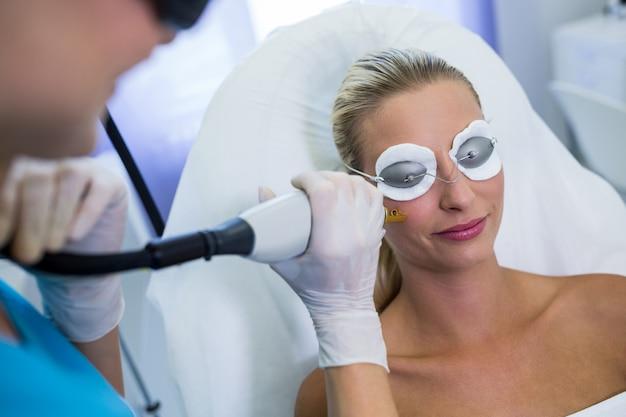 Mulher recebendo tratamento de depilação a laser no rosto Foto gratuita