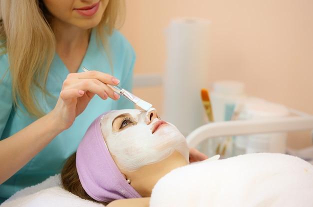 Mulher recebendo tratamento facial de um cosmetologista em um spa. Foto Premium
