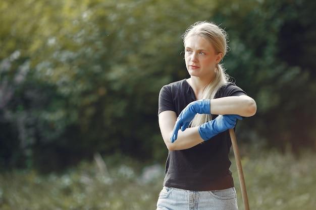 Mulher recolhe folhas e limpa o parque Foto gratuita