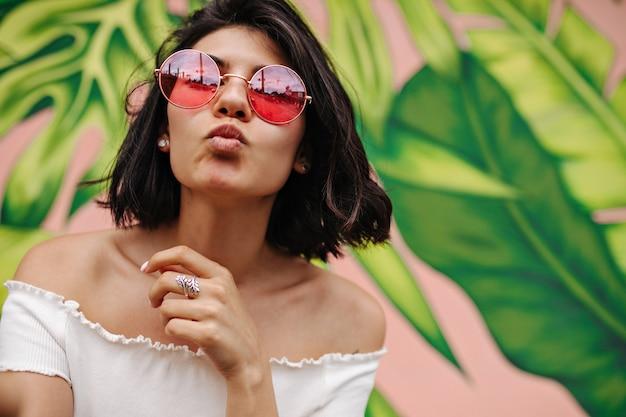 Mulher refinada em óculos de sol rosa posando com expressão facial de beijo Foto gratuita
