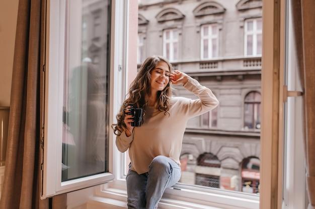 Mulher refinada em uma camisa da moda apreciando a vista da cidade da janela Foto gratuita