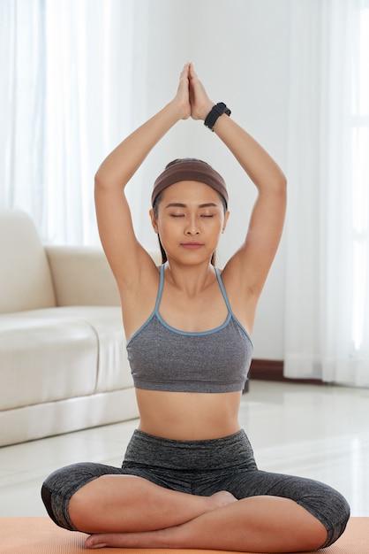 Mulher relaxada, meditando em casa Foto gratuita