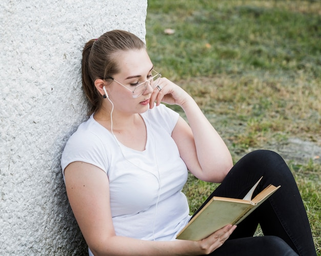 Mulher relaxante com livro na parede do parque Foto gratuita