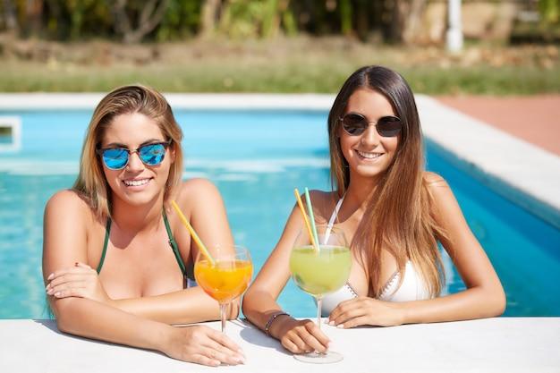 Mulher, relaxante, e, bebida, um, coquetel, em, piscina Foto Premium