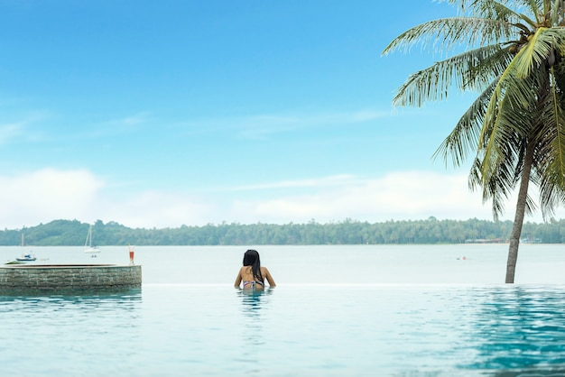 Mulher, relaxante, em, infinidade, piscina, olhar vista Foto Premium