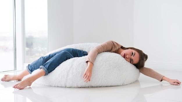 Mulher relaxante em um saco de feijão e estar entediado Foto gratuita