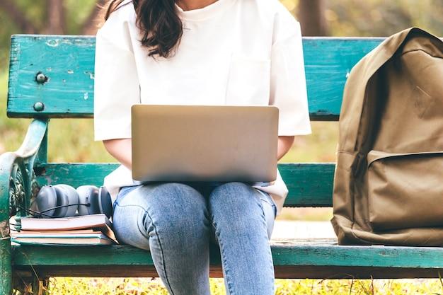 Mulher, relaxe, com, computador laptop, sentando, ligado, capim, parque Foto Premium