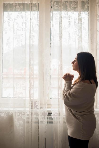 Mulher religiosa, orando por ajuda em casa Foto gratuita
