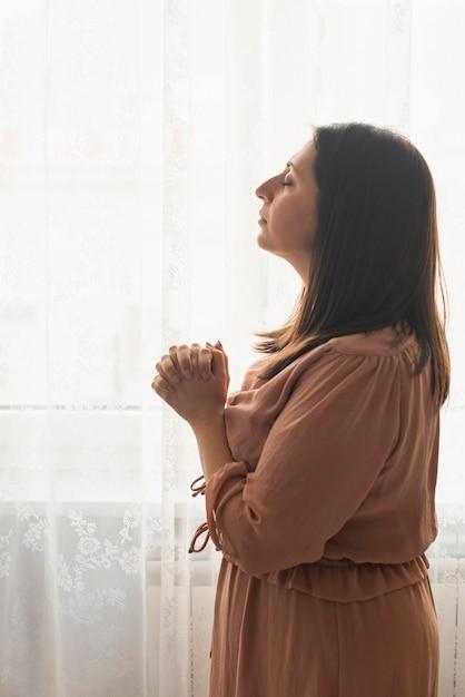Mulher religiosa rezando em casa Foto gratuita